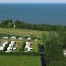 Lucht foto camping met aan de andere kant van de dijk het Markermeer met recreatie strandje. Met dank aan Luchtfotografie Henk Breedland